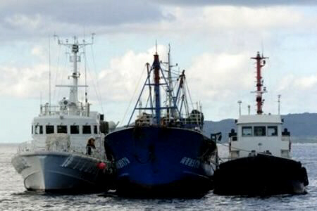A detained Chinese fishing boat is flanked by Japanese Coast Guard vessels during an investigation by authorities.
