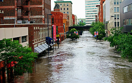 Water from the swollen Cedar River rushes past downtown buildings Thursday, June 12, 2008 in Cedar Rapids, Iowa. Officials estimated that 100 blocks in Cedar Rapids were under water forcing the evacuation of nearly 4,000 homes and leaving cars underwater on downtown streets. (AP Photo/Jeff Roberson)