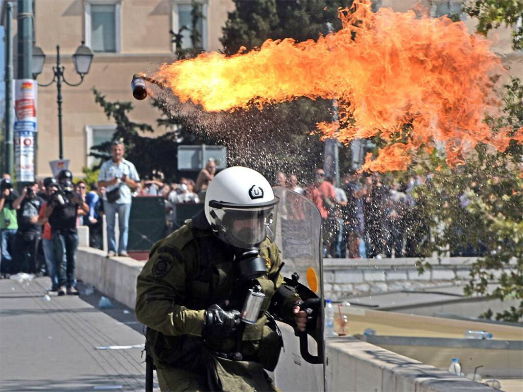 Firebombs explode in front of riot police during clashes in Greece