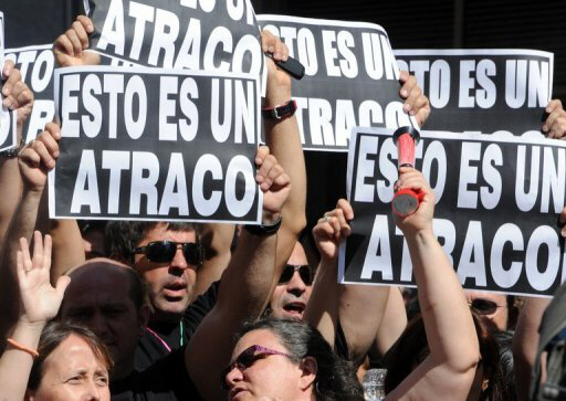 Government employees in Madrid hold signs reading ''This is a hold-up'' during a demonstration against the Spanish government's latest austerity measures. (AFP Photo/Dominique Faget)