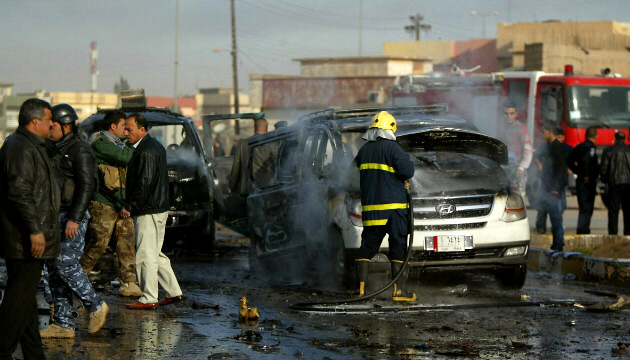 Iraqi firefighter douses car as security forces inspect blast site