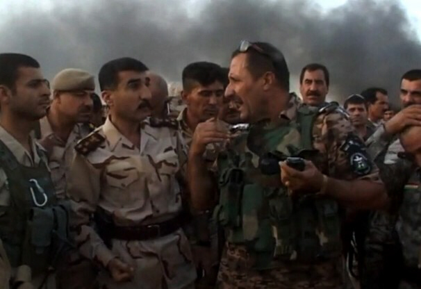 Iraqi soldiers talking as smoke billows behind them