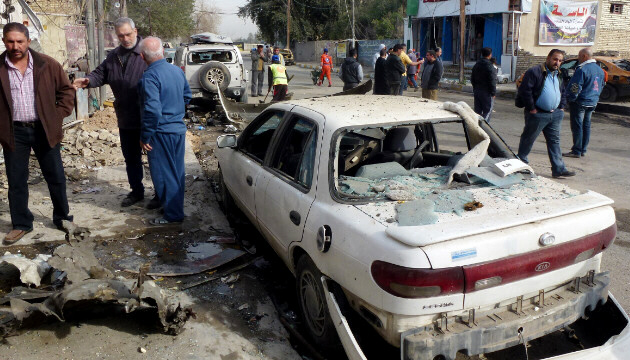 Iraqis inspect the damage after an explosion in central Baghdad