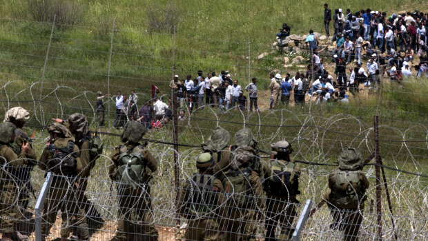 Israeli troops take positions as pro-Palestinian protesters approach the border