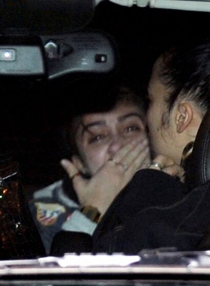 Lourdes, upset and terrified, is consoled by an unidentified friend seated in limo next to Madonna