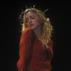 Madonna poses seductively for the audience wearing a crown of thorns