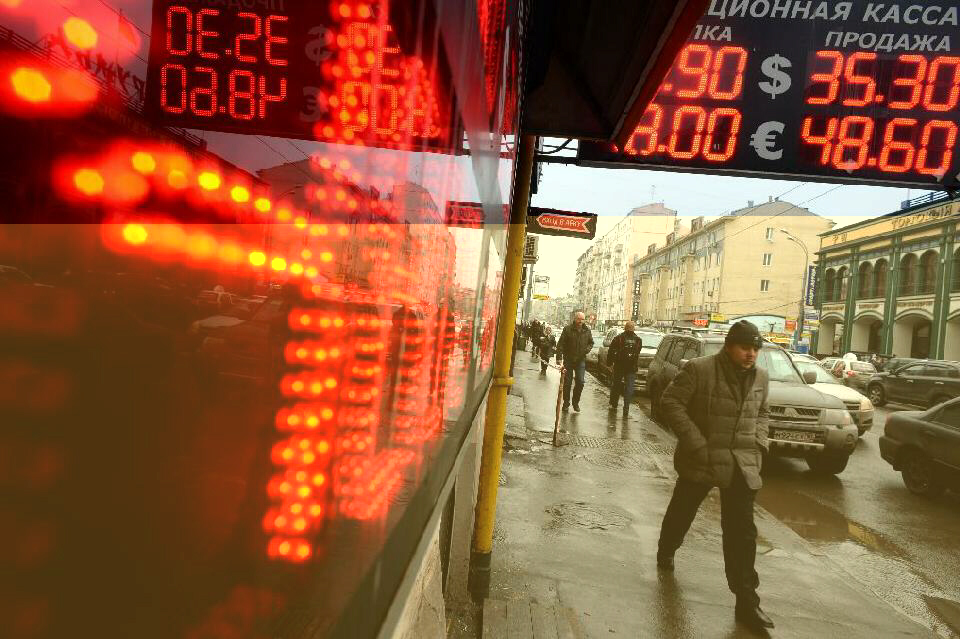 Man walks under board listing foreign currency rates against Russian ruble
