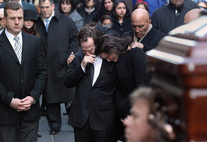 Matthew and Madonna Badger embrace as the casket of one of their daughters arrives for funeral services