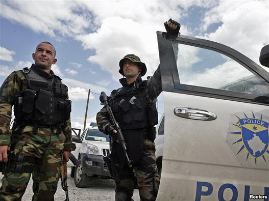 Members of the Kosovar special police forces stand by their vehicle in the ethnically divided town of Mitrovica on July 26.
