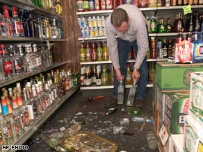 Mike Dunkel cleans up broken bottles Friday at his liquor store in Mount Carmel, Illinois.