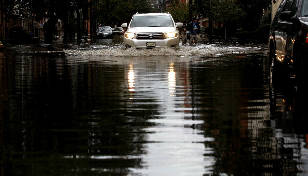 Motorists drive through standing water in Hoboken, New Jersey