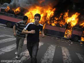 Moussavi supporters run past a burning bus