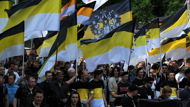 Nationalists carry the black-yellow-white flags of the Russian Empire