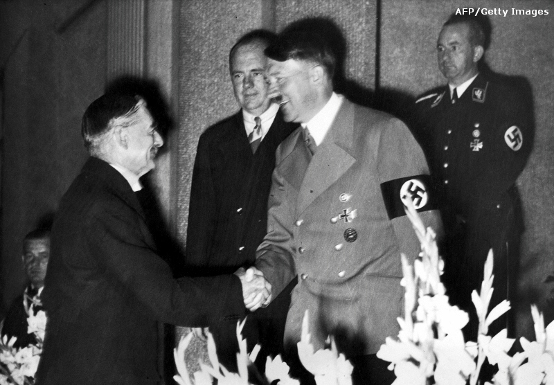 British Prime Minister Neville Chamberlain and German Chancellor Adolf Hitler shake on historic peace deal