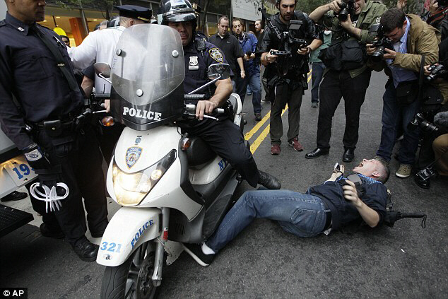 A New York City police officer runs over a National Lawyers Guild observer as Occupy Wall Street demonstrators march through the roads near Wall Street on Friday