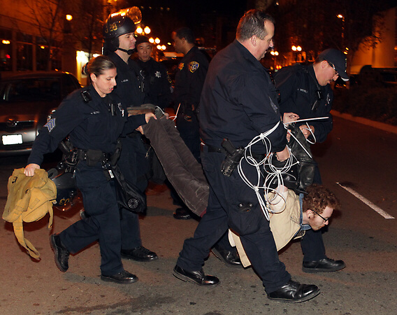 Oakland Police officers take away a Occupy protesters as arrests are made