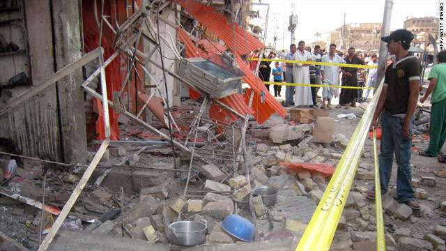 Onlookers gather at the scene of a car bomb explosion in Baghdad