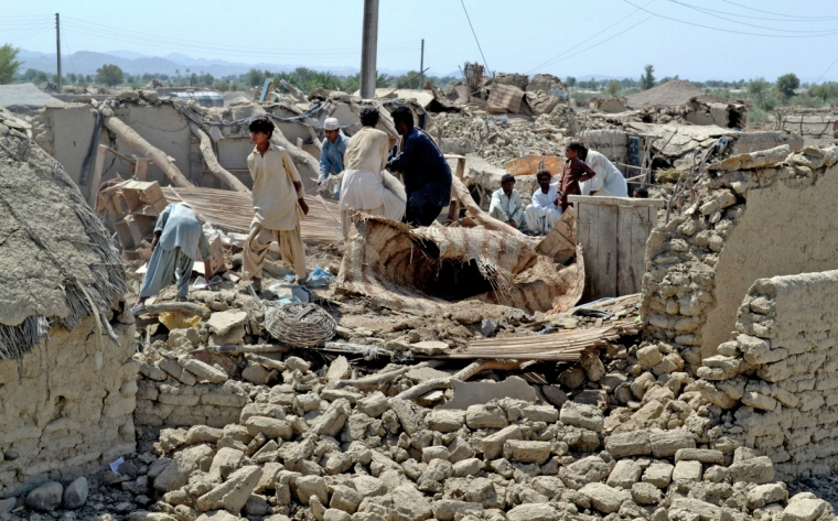 Pakistani villagers look for belongings amid rubble of homes