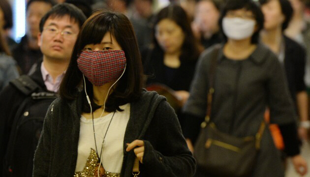 Pedestrians in Shanghai wear face masks