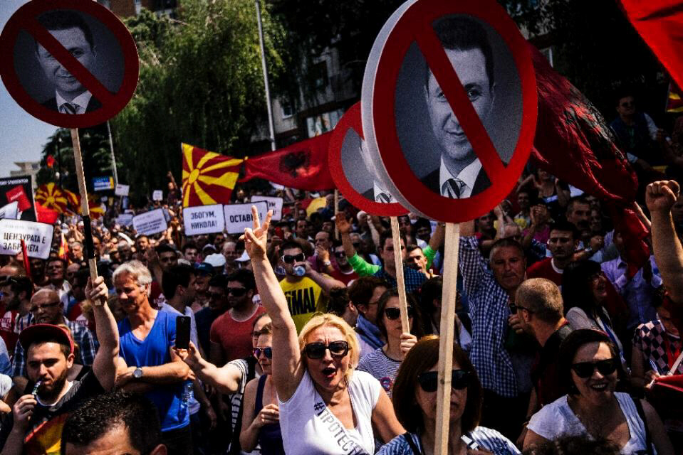 People hold signs with picture of Macedonian Prime Minister Nikola Gruevski during protest in Skopje