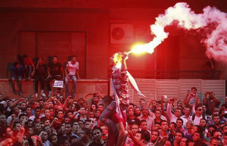 People shout slogans and light flares in front of the U.S. embassy