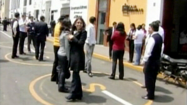 People stand outside after evacuating buildings in Peru