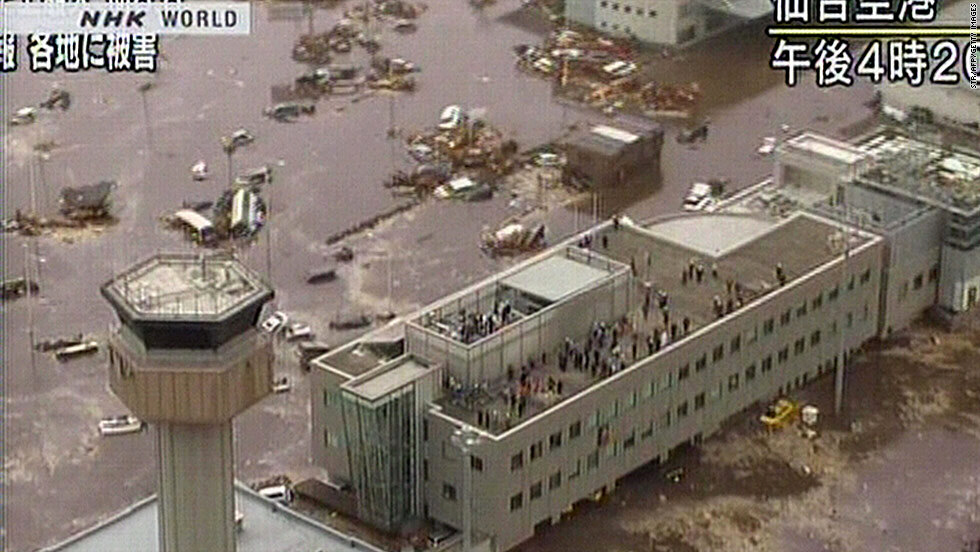 People standing on roof of flooded airport in Sendai