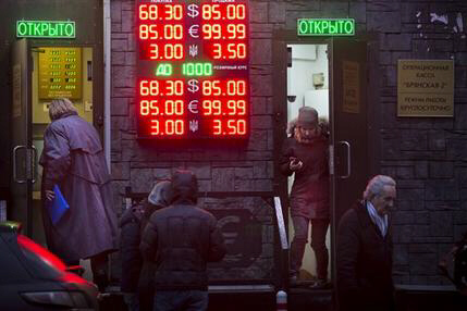 People wait to exchange their currency as ruble falls