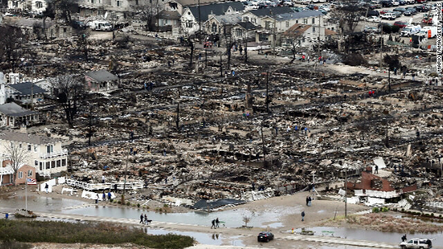 People walk near the remains of burned homes in the Breezy Point