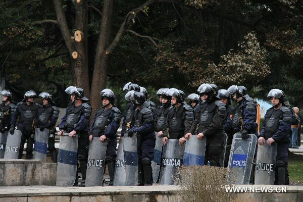 Police and national guards in full riot gear stand guard in front of the main government building during an anti-government rally in Tirana, capital of Albania, Feb. 18, 2011.