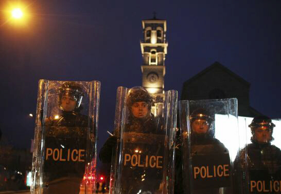 Police hold shields during a demonstration by protesters