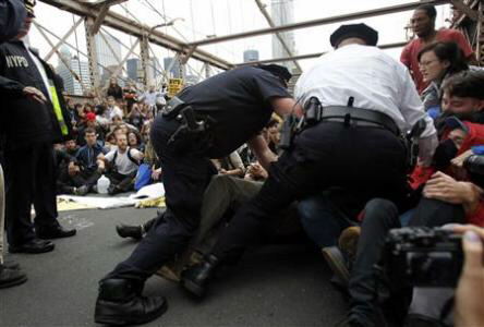 Police officers reach into a crowd of protesters to make an arrest