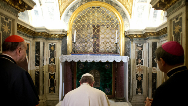 Pope Francis kneels in prayer in front of St. Peter's tomb
