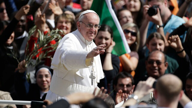 Pope Francis waves to a crowd of the faithful