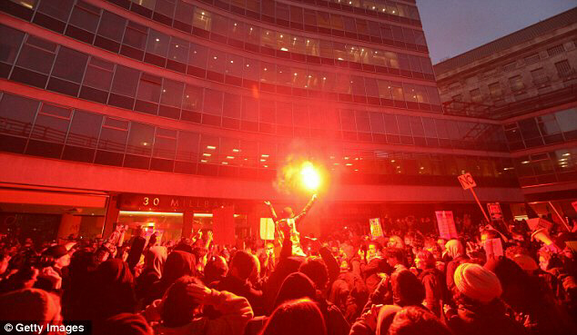 Protester lights flare outside entrance to Tory Party headquarters