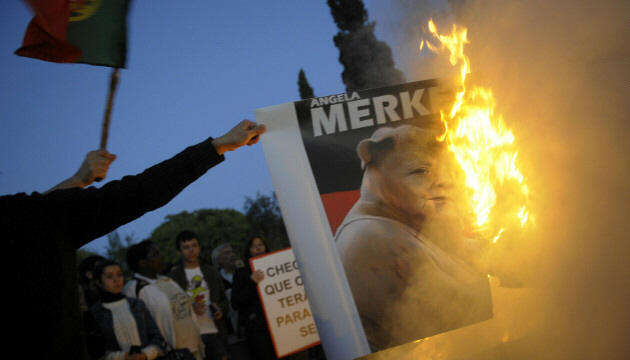 Protesters burn a picture depicting Angela Merkel in Lisbon
