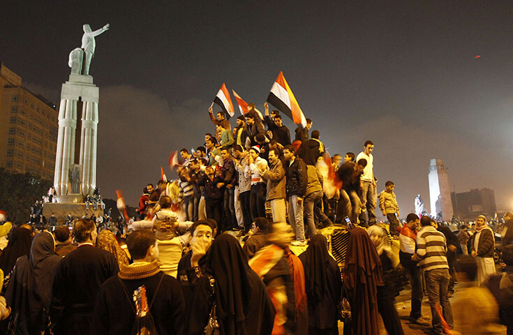Protesters in Cairo celebrate on top of an army tank