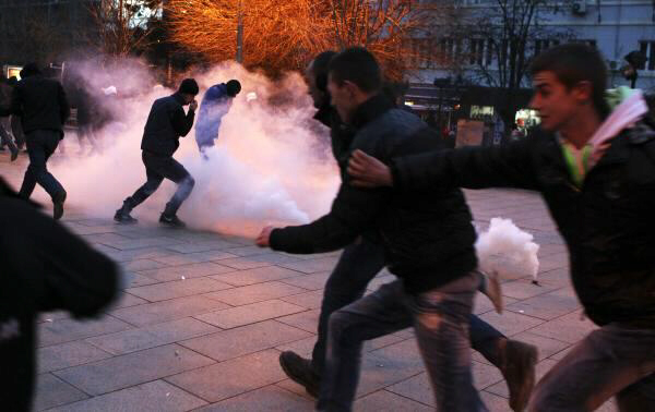 Protesters react to tear gas during demonstration in centre of Pristina