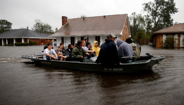Rescue workers transport residents trapped by rising water from Isaac