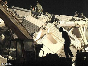 Rescuers search for victims in the debris of a hospital in Dujiangyan