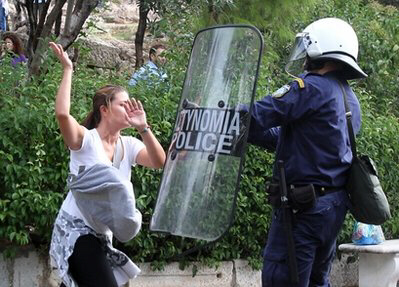 Riot police clash with a protester at the gate of the ancient Acropolis site