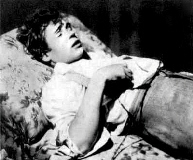 The corpse of Sergei Yesenin lies upon the bed