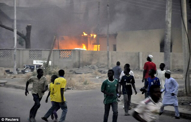 Smoke rises from the police headquarters as people run for safety in northern Nigerian city of Kano