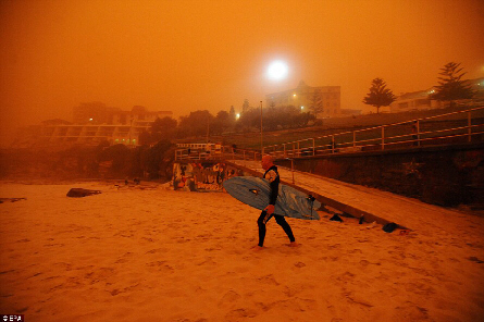 Surfer heads for water as red dust storm blankets Sydney