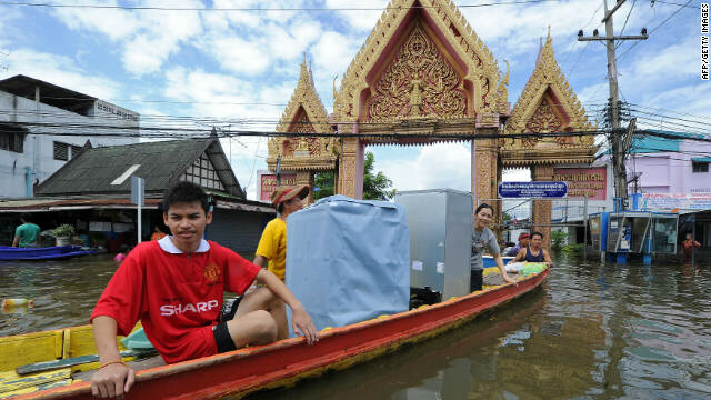 Thai residents transport their belongings on a boat