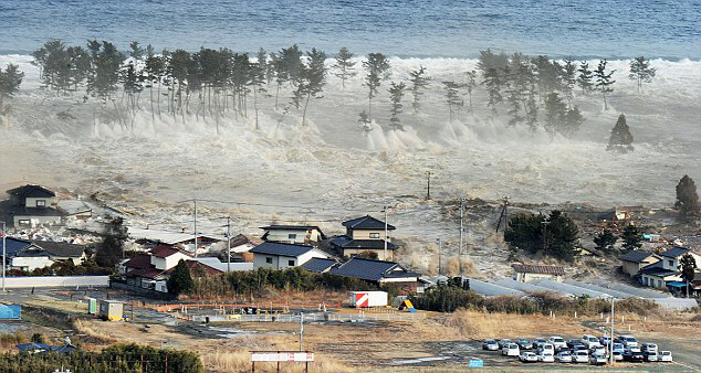 The tsunami engulfs a residential area in Natori, Miyagi