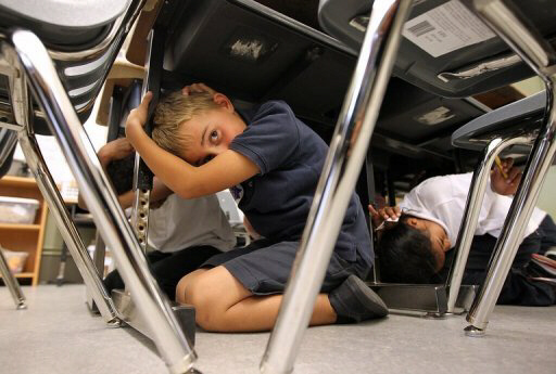 Third grade students take cover under desks during earthquake drill in southern California
