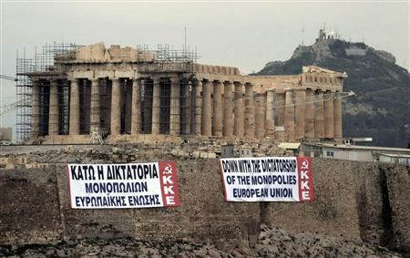 Two anti-austerity banners are displayed on a hill at the Acropolis
