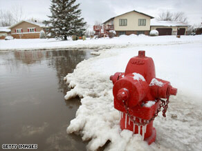 Water floods a street in Oxbow, North Dakota