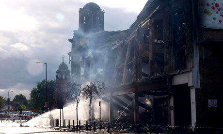Wellsian wasteland ... water is pumped on a smouldering building in post-riot Tottenham. Photograph: Max Nash/PA